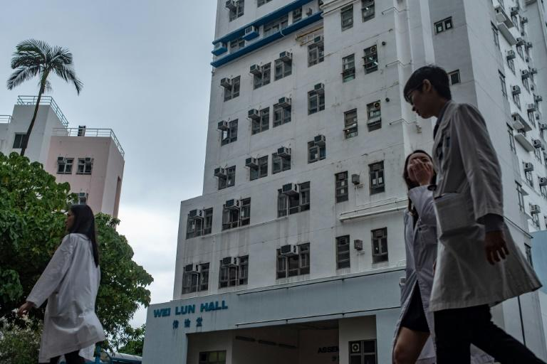 Students walk in front of University of Hong Kong's Wei Lun Hall, the residential block where university professor Cheung Kie-chung and his family lived, in Hong Kong's Pokfulam district