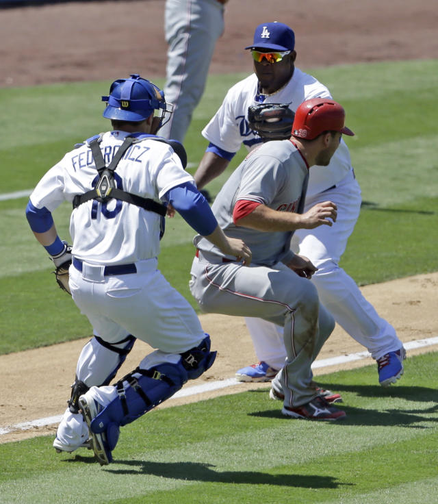 Los Angeles Dodgers catcher Tim Federowicz, left, and third baseman Juan Uribe, right, chase down the Cincinnati Reds' Devin Mesoraco, center, between third and home in the sixth inning of a baseball game in Los Angeles, Sunday, July 28, 2013. (AP Photo/Reed Saxon)