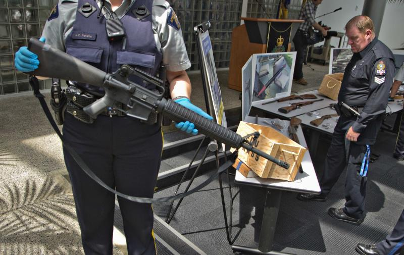 A member of Royal Canadian Mounted Police holds an assault rifle that was turned in to the police in Richmond