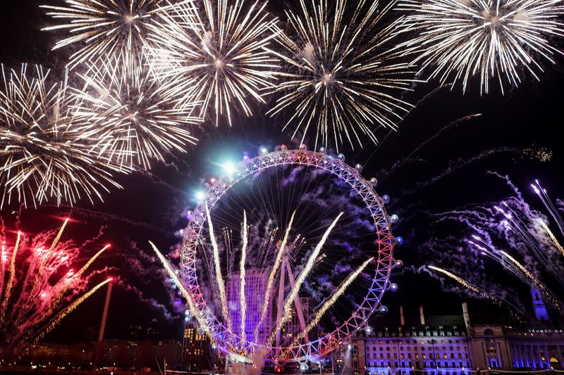 Fireworks explode over the London Eye wheel during New Year celebrations in central London