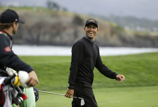 Surfer Kelly Slater smiles at the gallery while walking to the 17th green of the Pebble Beach Golf Links during the third round of the AT&T Pebble Beach Pro-Am golf tournament Saturday, Feb. 8, 2014, in Pebble Beach, Calif. (AP Photo/Eric Risberg)