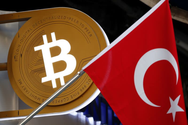 A bitcoin logo is seen next to Turkish flag at a cryptocurrency exchange shop in Istanbul