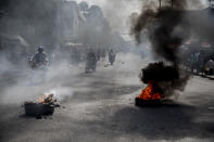 Motorcycles ride past a barricade of burning tires during a protest by residents over a police raid that resulted in the death of a young musician, in downtown Port-au-Prince, Haiti, Wednesday, Sept. 22, 2021. Violence can breakout at any time, in any random corner of the city. Angry mobs gather and dissolve, reunite and prepare for a new confrontation, while bystanders await the unexpected. (AP Photo/Rodrigo Abd)