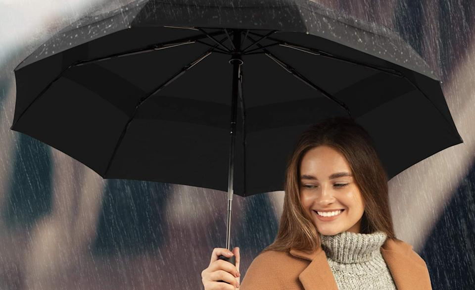 A woman in the rain huddled under a Repel travel umbrella.