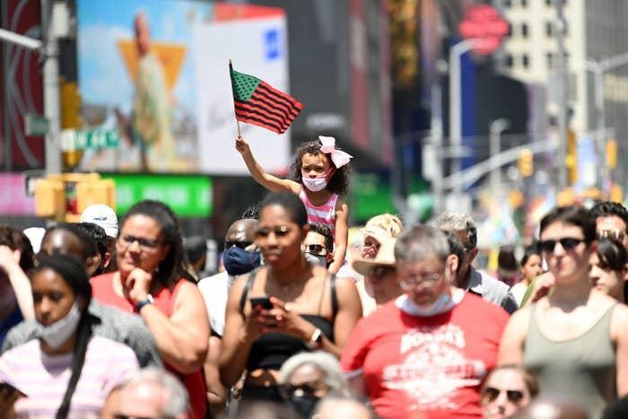 A young girl waves an African American flag during the Broadway Celebrates Juneteenth in Times Square on June 19 in New York City.