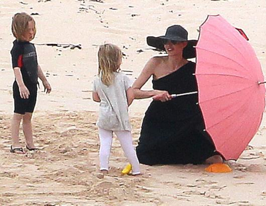 Post-Engagement Holiday? Angelina Jolie and Brad Pitt (not pictured) take the whole family to the beach on the Galapagos Islands off the coast of Ecuador in South America, April 20, 2012. Angie is well protected from the sun in her black smock under a pink umbrella. Angelina and Brad have said that their children have wanted them to get married for a long time