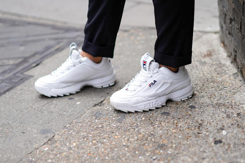 A guest wears white FILA sneakers shoes, during London Fashion Week Men's June 2019 on June 08, 2019 in London, England. (Edward Berthelot/Getty Images)