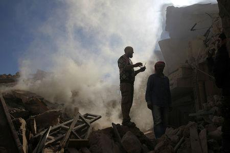 Smoke rises while men inspect damaged buildings after an airstrike on the rebel-held town of Darat Izza, province of Aleppo, Syria November 5, 2016. REUTERS/Ammar Abdullah