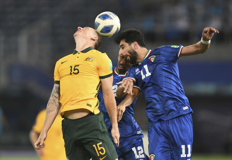 Australia's Mitchell Duke, left, jumps for the ball with Kuwait's Fahed Alansari, right, during the World Cup 2022 Group B qualifying soccer match between Kuwait and Australia in Kuwait City, Kuwait, Thursday, June 3, 2021. (AP Photo/Jaber Abdulkhaleg)