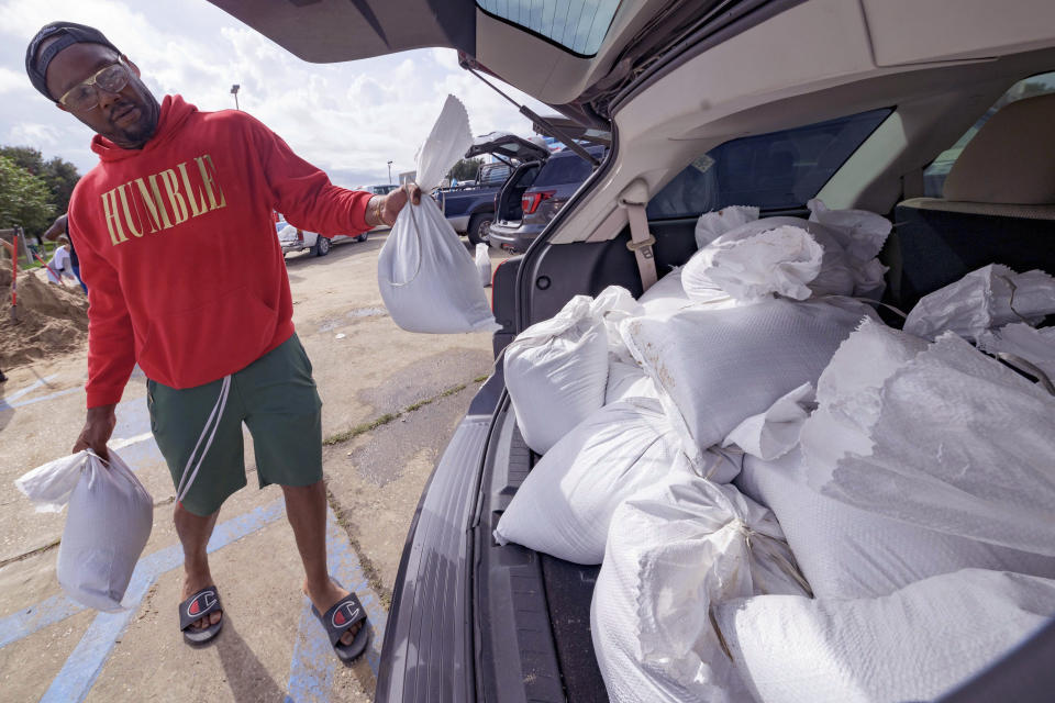 Jawan Williams loads his vehicle with sandbags before landfall of Hurricane Ida at the Frederick Sigur Civic Center in Chalmette, La., which is part of the Greater New Orleans metropolitan area, Saturday, Aug. 28, 2021. The storm is expected to bring winds as high as 140 mph when it slams ashore late Sunday. (AP Photo/Matthew Hinton)