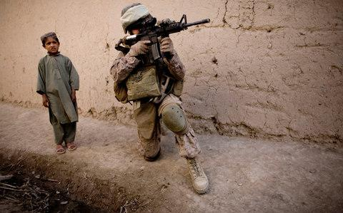 an Afghan boy watches Cpt. Chris Esrey of Havelock, North Carolina, with India, 3rd Battalion 5th Marines, First Marine Division, company, scan the area during a patrol in Sangin, south of Kabul, Afghanistan