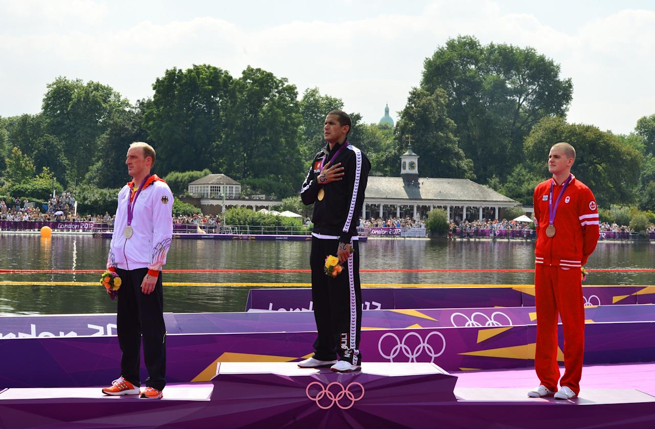 Tunisia's Oussama Mellouli (C) poses with his gold medal on the podium flanked by silver medalist (L) Germany's Thomas Lurz and bronze medalist Canada's Richard Weinberger (R) after winning the men's 10km open water swimming marathon at the London 2012 Olympic Games at Hyde Park in London, on August 10, 2012. Mellouli claimed victory to become the first person to win Olympic titles in both pool and open water races.  AFP PHOTO / LUIS ACOSTALUIS ACOSTA/AFP/GettyImages