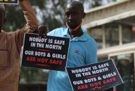A demonstrator holds signs during a protest to urge authorities to rescue hundreds of abducted schoolboys, in northwestern state of Katsina