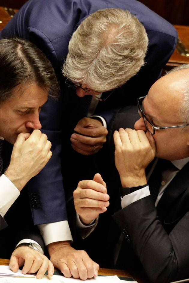 Italian Premier Giuseppe Conte, left, Finance Minister Roberto Gualtieri, right, and Democratic Party Lawmaker Paolo Gentiloni share a word during the parliament debate ahead of confidence vote later at the Lower Chamber in Rome, Monday, Sept. 9, 2019. Conte is pitching for support in Parliament for his new left-leaning coalition ahead of crucial confidence votes. (AP Photo/Gregorio Borgia)