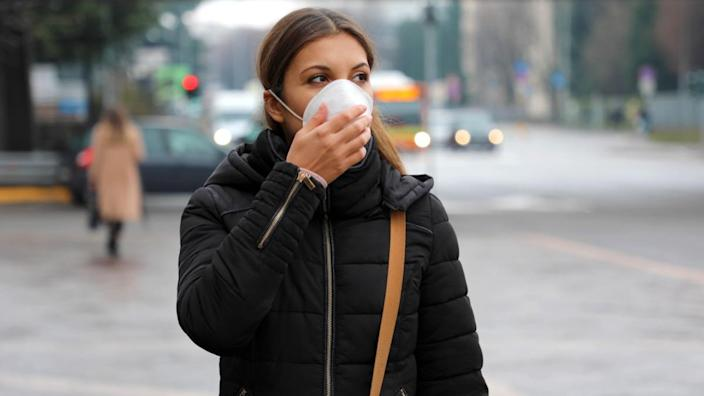 Woman on a street wearing face mask protective for spreading of disease virus SARS-CoV-2