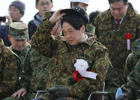 Japan's Defence Minister Itsunori Onodera (C) adjusts his cap as he inspects the annual new year military exercise by the Japanese Ground Self-Defense Force 1st Airborne Brigade during at Narashino exercise field in Funabashi, east of Tokyo January 12, 2014. REUTERS/Issei Kato