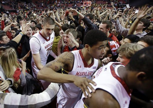 Maryland center Alex Len, top left, of Ukraine, and guard Nick Faust make their way through fans who stormed the court after an NCAA college basketball game against North Carolina State in College Park, Md., Wednesday, Jan. 16, 2013. Maryland won 51-50. (AP Photo/Patrick Semansky)