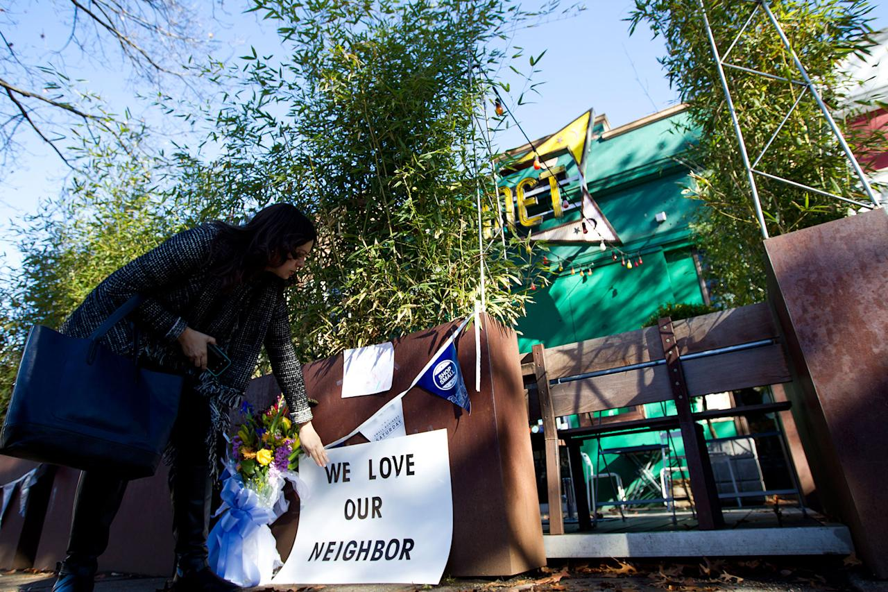 <p>Meighan Stone places a support banner with flowers outside the door of Comet Ping Pong pizza shop, in Washington, Monday, Dec. 5, 2016. (AP Photo/Jose Luis Magana) </p>