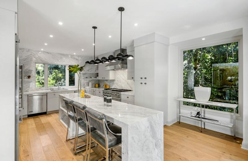 The gleaming chef's kitchen, outfitted in ribboned Carrara marble, takes in garden views.