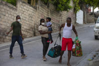 Jean Charles Celestin, right, carries luggage belonging to his cousin Jhon Celestin, left, Jhon's wife Delta De Leon, and their daughter Chloe, in Port au Prince, Haiti, Wednesday, Sept. 22, 2021. Jhon Celestin arrived in Haiti aboard the last flight Wednesday to the Haitian capital, a city the 38-year-old left three years ago in search of a better-paying job to help support his family. (AP Photo/Joseph Odelyn)