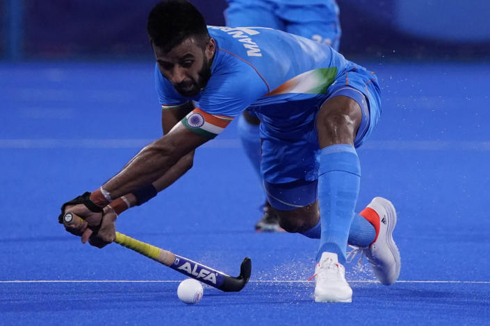 India's Manpreet Singh (7) passes against Japan during a men's field hockey match at the 2020 Summer Olympics, Friday, July 30, 2021, in Tokyo, Japan. (AP Photo/John Locher)