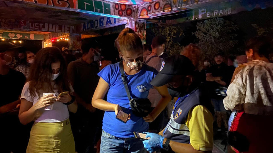 In this Tuesday, Jan. 26, 2021 photo, a Thai immigration officer talks to people at a bar on Koh Phangan island, Surat Thani province, southern Thailand. Police raided a party at a bar on a popular resort island in southern Thailand and arrested 89 foreigners for violating coronavirus regulations, officials said Wednesday. (Police Investigation Team of Surat Thani Immigration via AP)