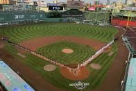 The Baltimore Orioles players and staff, left, and some of the Boston Red Sox players and staff, right, kneel along the baselines to acknowledge Black Lives Matter before the opening day baseball game, Friday, July 24, 2020, at Fenway Park in Boston. (AP Photo/Kyle Hightower)