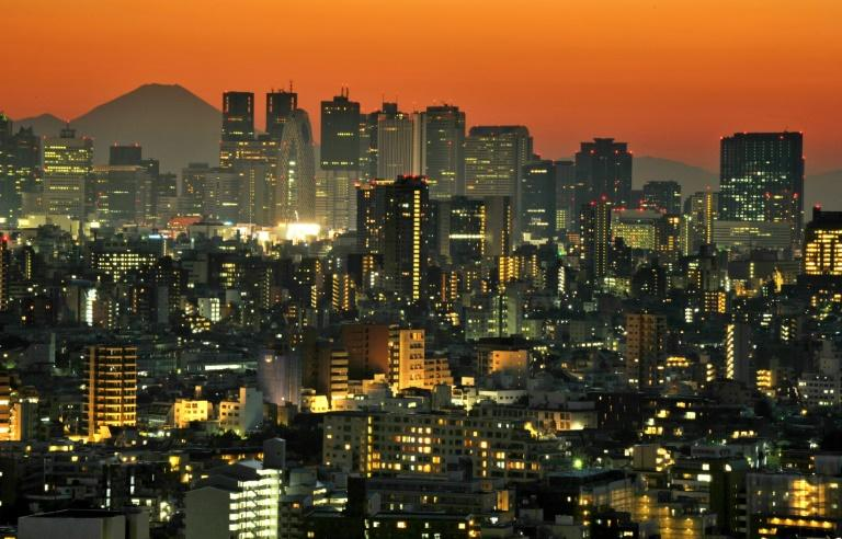 "This file photo taken on October 21, 2012 shows Japan's highest mountain Mount Fuji (top L) rising up behind the skyscrapers dotting the skyline of the Shinjuku area of Tokyo at sunset. ""Earth Hour"" falls on March 25 this year"