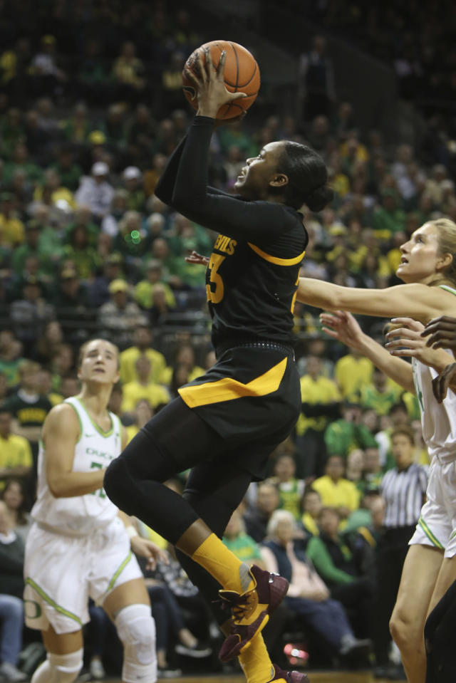Arizona State's Ja'tavia Tapley, center, shoots between Oregon's Sabrina Ionescu, left, and Lydia Giomi, right, during the second quarter of an NCAA college basketball game in Eugene, Ore., Sunday, Feb. 9, 2020. (AP Photo/Chris Pietsch)