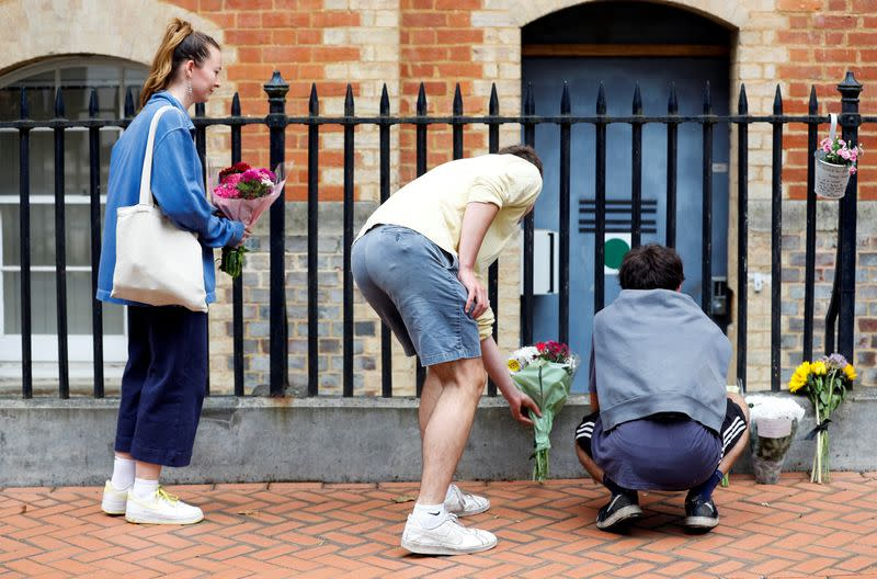 People leave flowers next to the police cordon at the scene of multiple stabbings in Reading