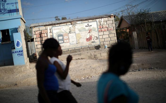 Women walk past an Oxfam sign in Corail, a camp for people displaced by the 2010 earthquake, on the outskirts of Port-au-Prince - REUTERS
