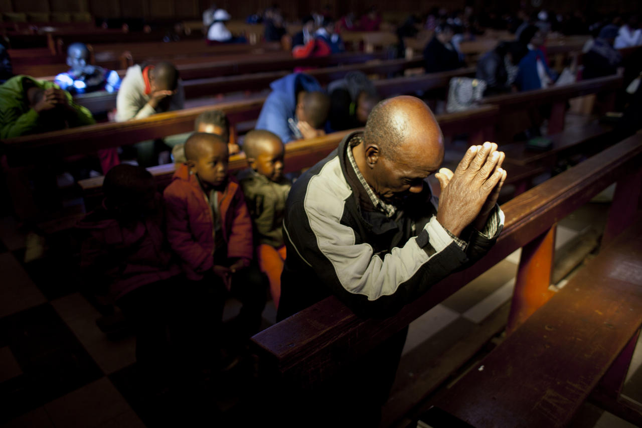 Worshippers pray in the Regina Mundi church in Soweto township on the outskirt of Johannesburg, South Africa, Sunday June 16, 2013. Former South African president Nelson Mandela remained hospitalized for the ninth day with an occurring lung infection. (AP Photo/Jerome Delay)