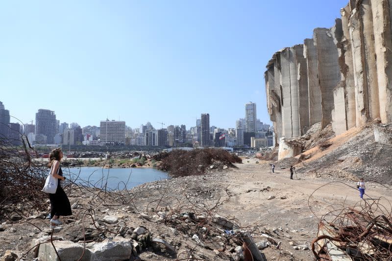FILE PHOTO: A woman walks on rubble at the site of last year's Beirut port blast, in Beirut