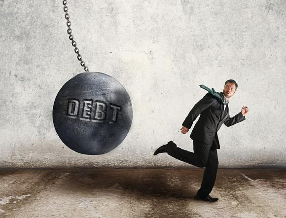 Businessman running away from wrecking ball with the word debt written on the side.