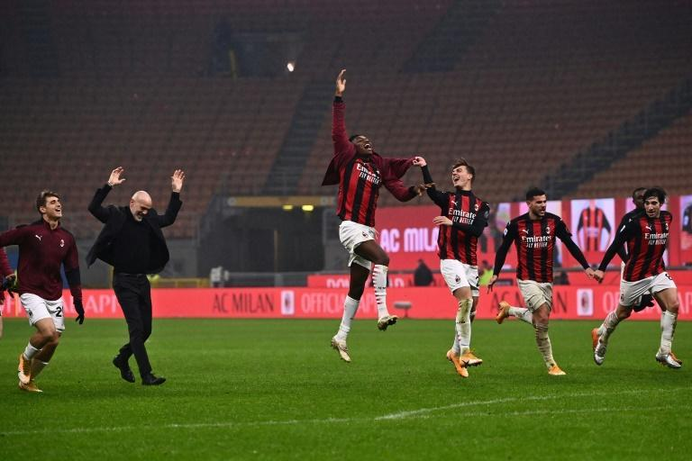 AC Milan coach Stefano Pioli (2ndL) and players celebrate after ending the year top of Serie A.