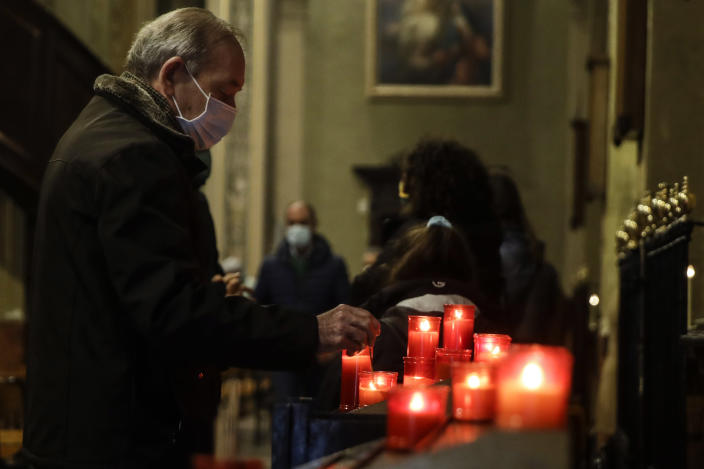 A man lights a candle during a Mass at the San Biagio church in Codogno, northern Italy, Sunday, Feb. 21, 2021. The first case of locally spread COVID-19 in Europe was found in the small town of Codogno, Italy one year ago on February 21st, 2020. The next day the area became a red zone, locked down and cutoff from the rest of Italy with soldiers standing at roadblocks keeping anyone from entering of leaving. (AP Photo/Luca Bruno)