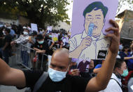 Pro-democracy protester hold picture activist Parit Chiwarak and shouting release our detained friends during a protest in front of the Parliament in Bangkok, Thailand, Saturday, Feb. 20, 2021. The protesters are calling for Prime Minister Prayuth Chan-ocha and his government to step down. (AP Photo/Sakchai Lalit)