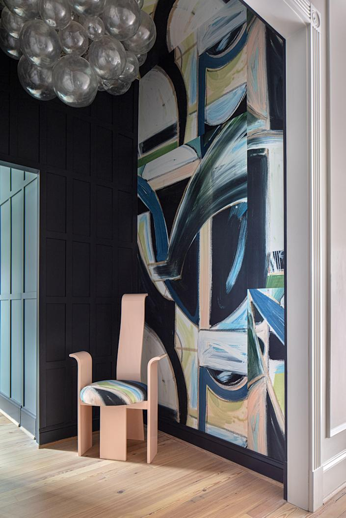 During the renovation, a closet was created for Thomas off the main bedroom entrance. To make the cumbersome space work aesthetically, a hidden door was built into the board and batten, and neighboring walls were covered in one of Lindsay's murals. The artist recently released a line of Art Deco–inspired mural wall coverings; this one is dubbed Jill to pay homage to the Arkansas interior designer.
