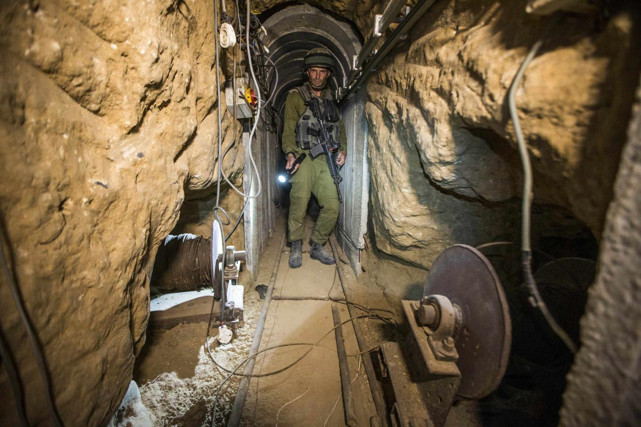 An Israeli army officer gives explanations to journalists during an army organised tour in a tunnel said to be used by Palestinian militants for cross-border attacks, July 25, 2014. U.S. Secretary of State John Kerry pressed regional leaders to nail down a Gaza ceasefire on Friday as the civilian death toll soared, and further violence flared between Israelis and Palestinians in the occupied West Bank and Jerusalem. REUTERS/Jack Guez/Pool (CIVIL UNREST MILITARY POLITICS CONFLICT)