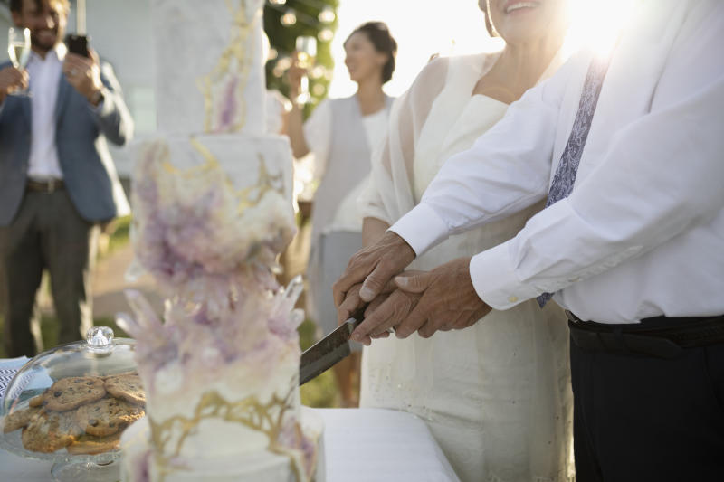 Senior bride and groom cutting wedding cake