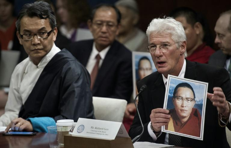 US actor Richard Gere (R) holds a photo of Tibetan monk Tenzin Delek Rinpoche, who died in a Chinese prison, before the Tom Lantos Human Rights Commission hearing, July 14, 2015 on Capitol Hill in Washington, DC