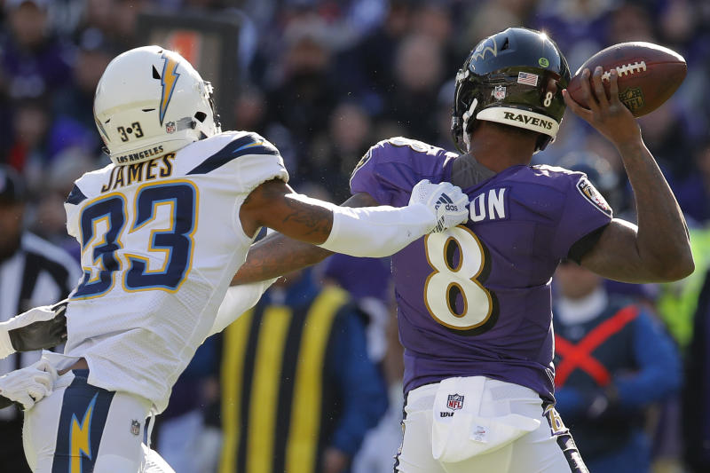 Los Angeles Chargers free safety Derwin James (33) grips the jersey of Baltimore Ravens quarterback Lamar Jackson (8) in the first half of an NFL wild card playoff football game, Sunday, Jan. 6, 2019, in Baltimore. (AP Photo/Carolyn Kaster)