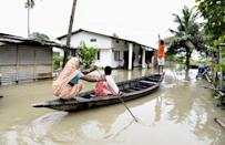 Villagers cross a flooded area on a boat, in Panikhaiti village, in Kamrup District, Assam, India on Tuesday, on July 14, 2020. Villages in Assam were flooded due to heavy rains. The rising water level inundated houses, residents were forced to move to a safer place. (Photo by Hafiz Ahmed/Anadolu Agency via Getty Images)