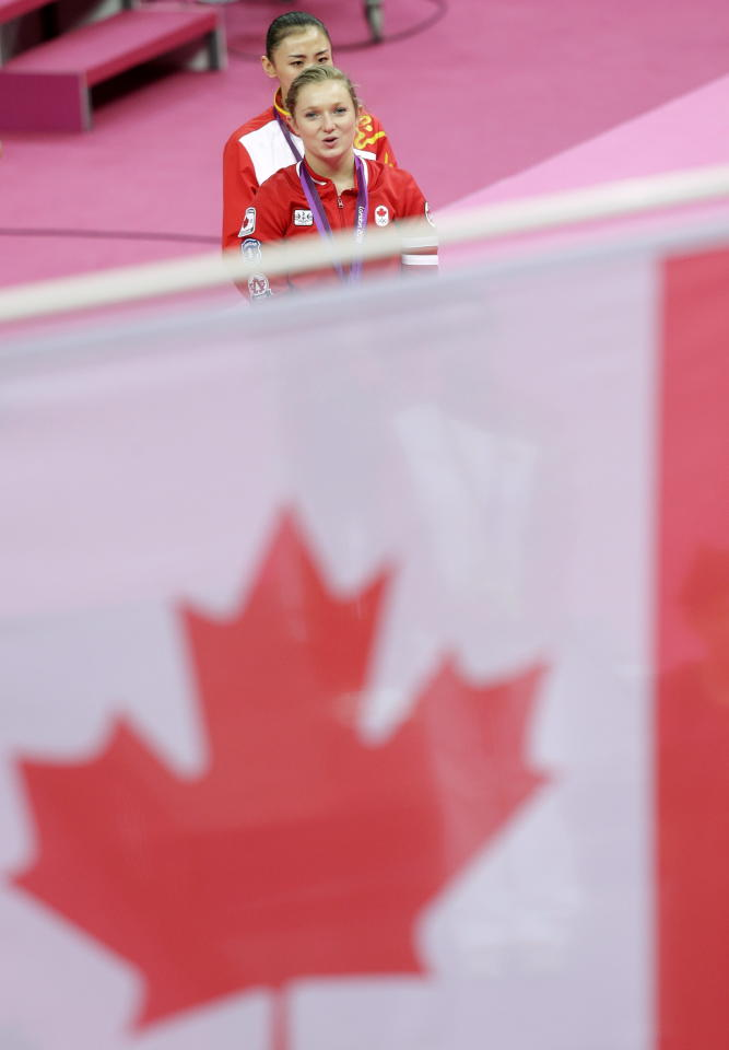 Canada's gold medallist Rosannagh Maclennan walks followed by China's bronze medallist He Wenna after the medal ceremony for the women's trampoline at the 2012 Summer Olympics, Saturday, Aug. 4, 2012, in London. (AP Photo/Julie Jacobson)