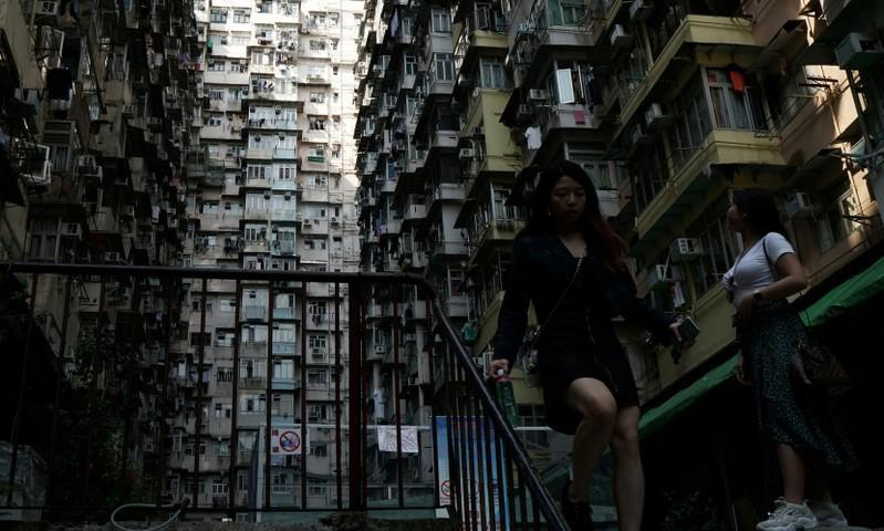 FILE PHOTO: Woman walks down the stairs of a residential building in Hong Kong