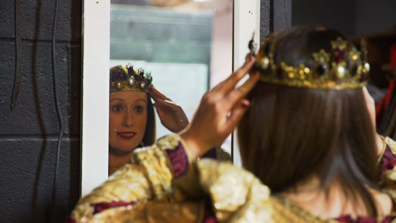 Henderson, a queen of Medieval Times, adjusts her crown. (Photo: Yahoo Finance)