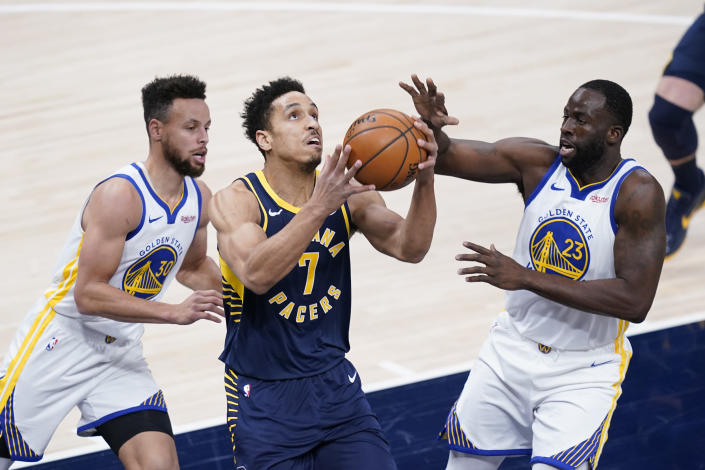 Indiana Pacers' Malcolm Brogdon (7) looks for a shot from between Golden State Warriors' Draymond Green (23) and Stephen Curry (30) during the first half of an NBA basketball game Wednesday, Feb. 24, 2021, in Indianapolis. (AP Photo/Darron Cummings)