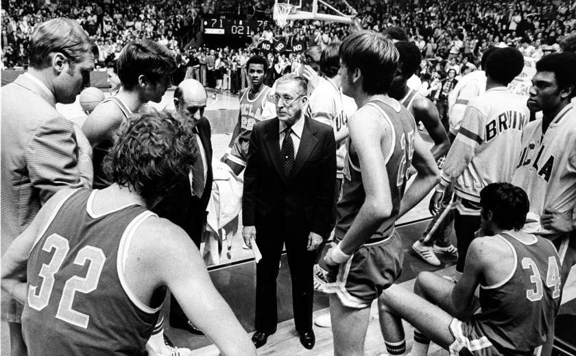 UCLA basketball coach John Wooden, center, talks to his players during a time out against Notre Dame.