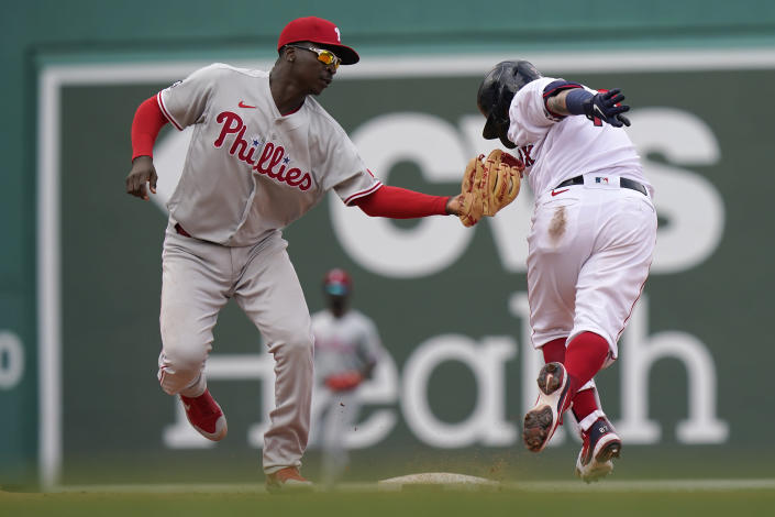 Philadelphia Phillies' Didi Gregorius, left, tags out Boston Red Sox's Christian Vazquez, right, in the sixth inning of a baseball game, Sunday, July 11, 2021, in Boston. (AP Photo/Steven Senne)
