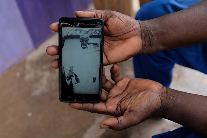 "Abdul Sumud Shaibu shows a photograph of his grandfather, in Obuasi, Ghana. ""My ancestors were giants,"" he said. (Photo: Francis Kokoroko/Reuters)"